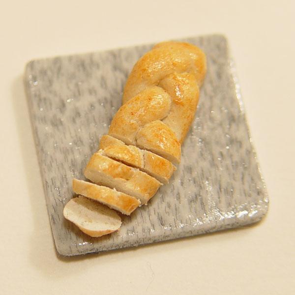/ scale minature sliced braided bread on granite cutting board,
