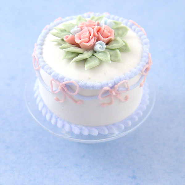 Miniature White Cake W/Pink Bows On A Glass Cake Stand